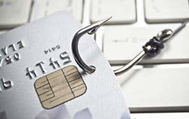 Credit card on fishing hook sitting on keyboard.
